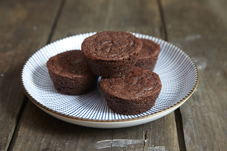 Chocolate muffin with white plate on wooden board. Stock Photo