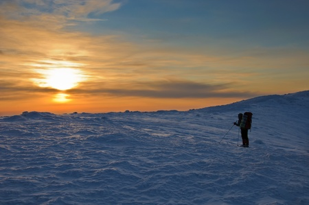 trekker silhouette at sunset in the beautiful mountains photo