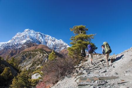 Two trekkers running on the road against Annapurna area Stock Photo