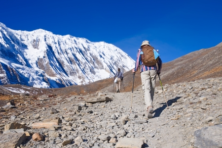 Two trekkers running on the road against Tilicho Lake Stock Photo
