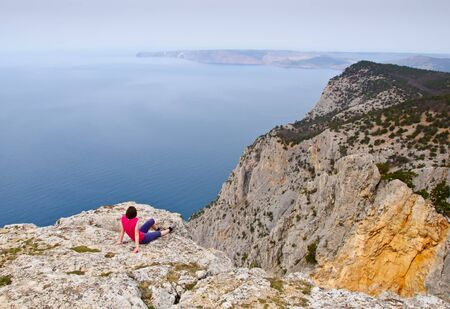 gazing: Girl  sitting and gazing into the distance on precipice above sea Stock Photo