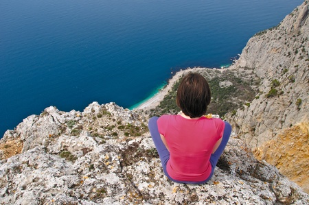 Girl  sitting and gazing into the distance on precipice above sea photo