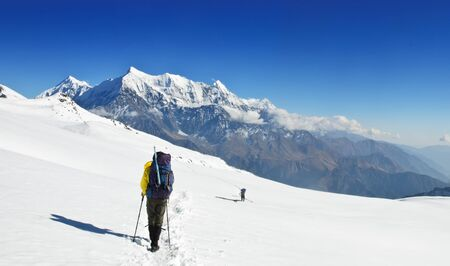 Lonely trekkers on big snow fields in Himalaya near Dhaulagiri Stock Photo