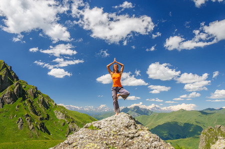 Young woman exercises yoga in the mountains