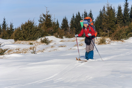x country: A woman cross country skiing in the mountain