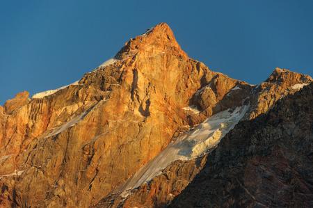 scarlet: Hight scarlet mountain peak in sunset rays Stock Photo