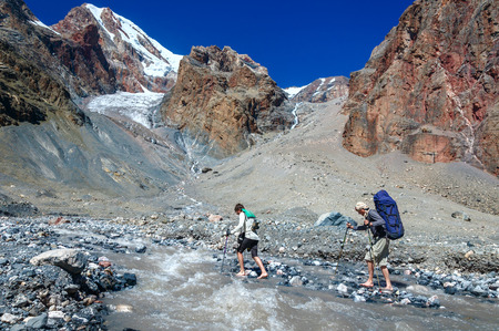 impregnable: Two hikers crossing mountain river