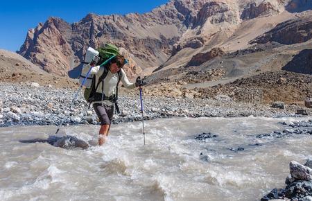 impregnable: Two hikers crossing mountain river. Fany mountain. Tadjikistan