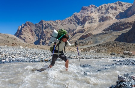 impregnable: Hiker crossing mountain river. Fany mountain. Tadjikistan