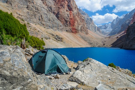 Lonely tent stands on the shore of a beautiful mountain lake. Pamir, Tadjikistan Stock Photo