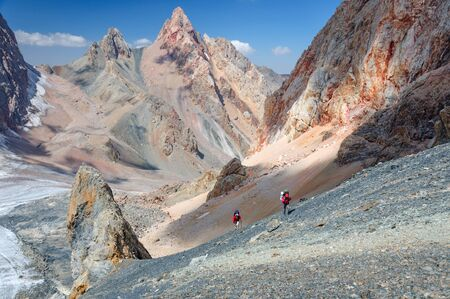 Two men climbing on the top with backpackon Pamir Mountain