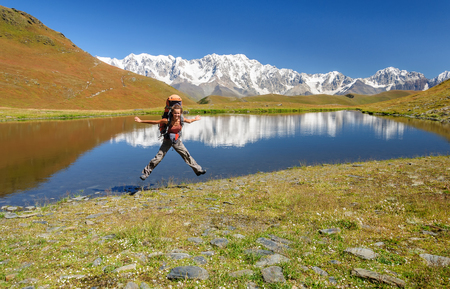 Happy summer girl jumping with backpack on mountain background