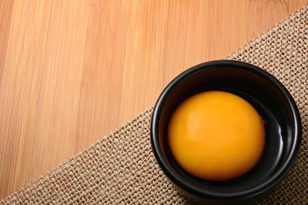 gamme de produit: Fresh egg yolk in black bowl and on wooden table