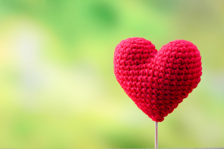 Red heart make from yarn on nature background