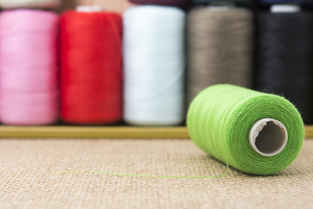 needle laces: Green spools of thread on sackcloth table