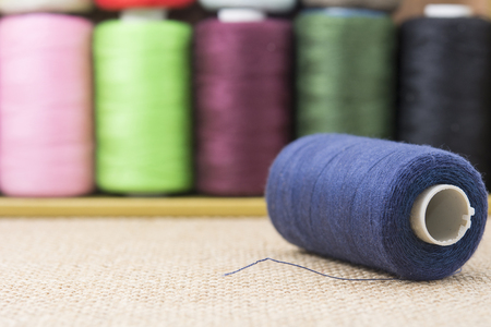 needle laces: Blue spools of thread on sackcloth table Stock Photo
