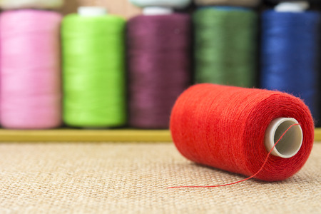 needle laces: Red spools of thread on sackcloth table Stock Photo