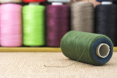 needle laces: Dark green spools of thread on sackcloth table Stock Photo