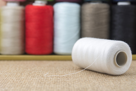 needle laces: White spools of thread on sackcloth table Stock Photo