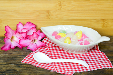 Crispy water chestnuts in coconut cream with spoon and flower Stock Photo
