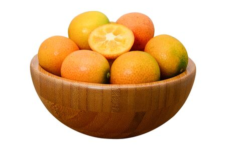 ripe kumquat fruit in wooden bowl isolated on white background with clipping path Stock Photo