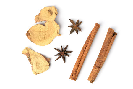Dry galangal and cinnamon sticks lying on a white background