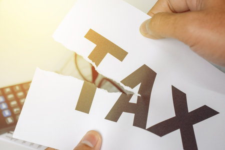 'Reduce Tax' man hands ripped paper with the word tax. business concept - closeup