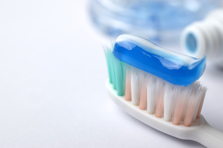 Toothbrush e dentifricio in pasta su priorità bassa vaga - primo piano