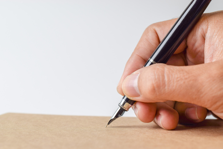 Human hand signing on formal paper at the table on white background - Close-up Archivio Fotografico