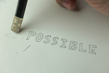 Changing the word impossible to possible with a pencil eraser, closeup Reklamní fotografie