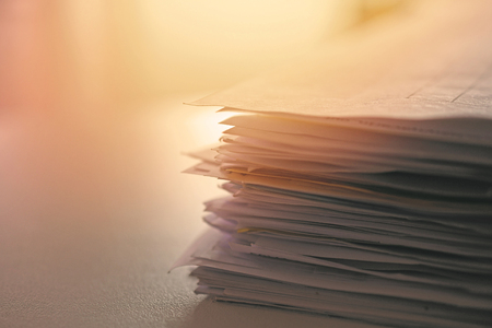 Stack of paper files on work desk in office, closeup