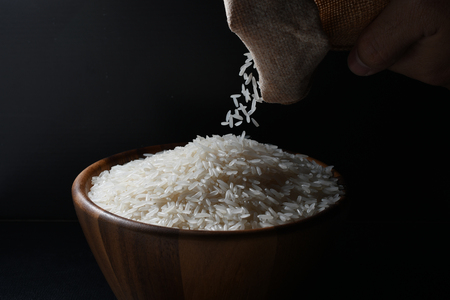 Pouring jasmine rice into a wooden bowl on black background