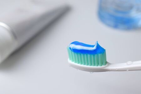 Toothbrush with water drop and toothpaste on blurred background