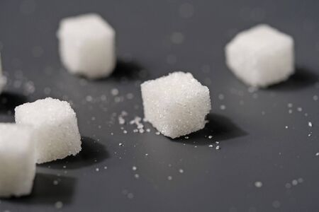 Close up the white sugar cubes on black table