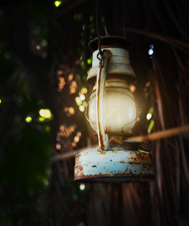 A shining rusty oil lantern hanging on the eaves of a hut.
