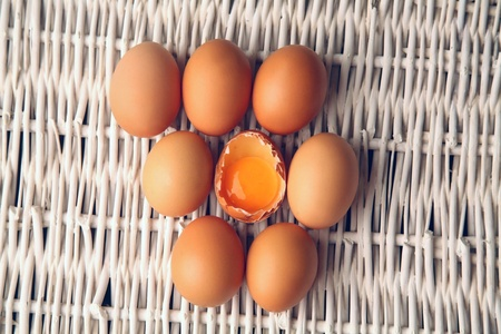 Broken egg surrounded by other eggs inside a basket  photo