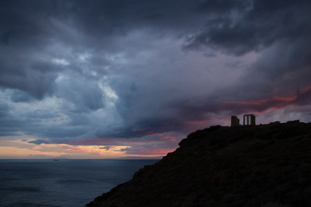 poseidon: Temple of Poseidon - Cape Sounion, Attica, Greece - silhouette of the temple of Poseidon in the dusk, with distant ships and open sea background, under heavy grey, red and purple clouds.