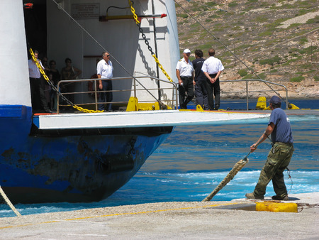 docking: Dock worker in action  A man is pulling a rope while ship crew is standing on a docking platform of approaching ferry. Island of Sifnos, Cyclades, Greece