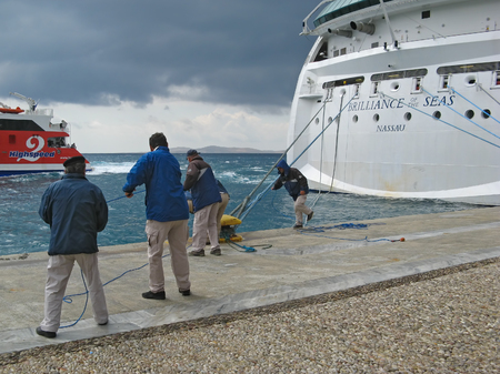 cruiser: Cruiser workers. Group of people pulling the ropes of giant cruiser ship. Island of Mykonos, Cyclades, Greece