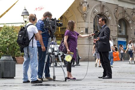 tv reporter: BELGRADE, SERBIA - JUN 9, 2011: RTS cameraman, sound recordist and TV reporter on the street holding an interview with a man in a suit