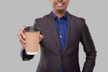 Businessman Holding Coffee To Go Cup Isolated Close Up. Indian Business man with Coffee Take Away Cup in Hands. Drink