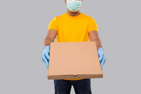 Delivery Man Pizza Box in Hands WEaring Medical Mask And Gloves Isolated Close Up. Yellow Tshirt Indian Delivery Boy. Man With Pizza in Hands. Delivery