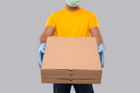Delivery Man Three Pizza Box in Hands Wearing Medical Mask And Gloves Close Up Isolated. Yellow Tshirt Indian Delivery Boy. Man With Pizza in Hands. Delivery