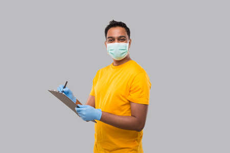 Indian Man Writing in clipboard Wearing Medical Mask and Gloves Watching in Camera. Indian man Clipboard