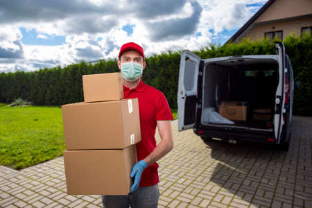Delivery Man Wearing Medical Mask and Gloves Holding Carton Boxes. Delivery Boy with Boxes in Hands at Delivery Point
