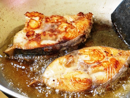 Two pieces of salmon fish cooked in a pan with oil and ingredients Stock Photo