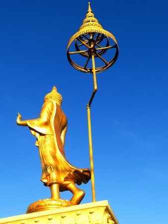 big standing golden Buddha against blue sky photo