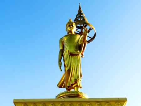 big standing golden Buddha against blue sky Stock Photo