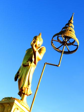 big standing golden Buddha against blue sky Stock Photo