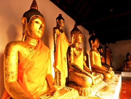 Golden Buddha statues with orange bands Surat Thani Thailand
